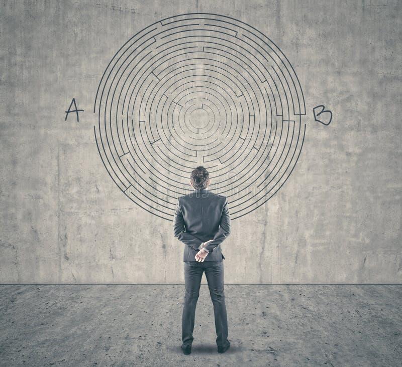Homem de negócios que olha um labirinto na parede foto de stock royalty free