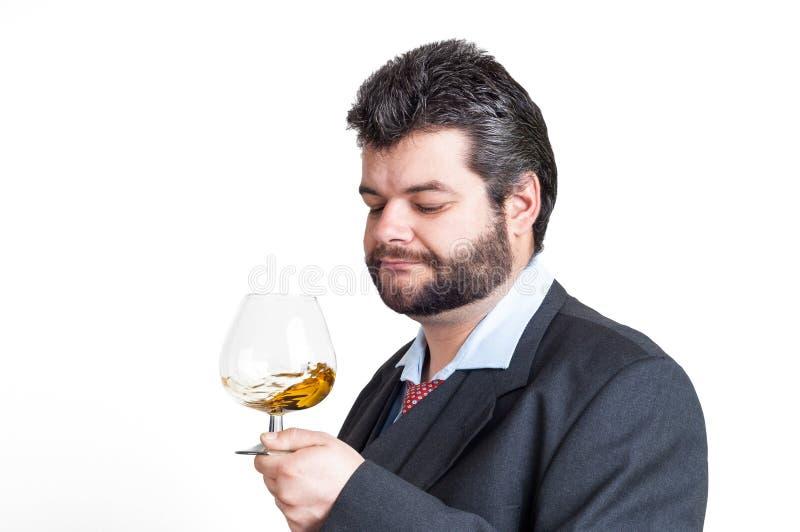 Homem de negócios que olha um vidro do uísque fotografia de stock
