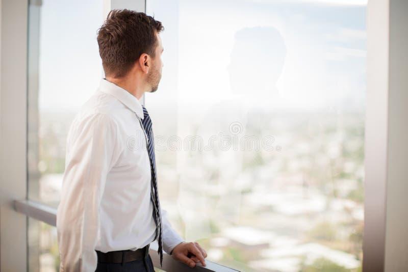Homem de negócios que olha uma janela fotografia de stock royalty free