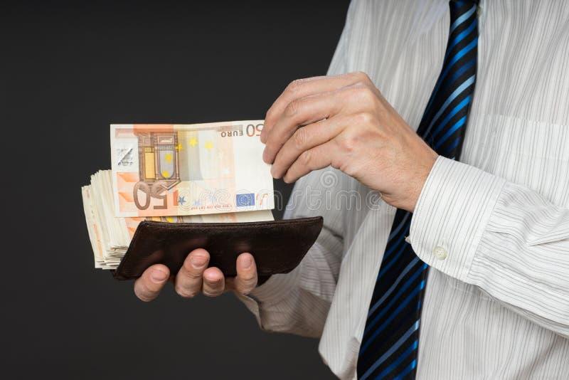 Homem de negócios que põe cédulas em sua carteira Pilha de dinheiro de cinqüênta euro O homem de negócio está guardando o dinheir imagens de stock royalty free