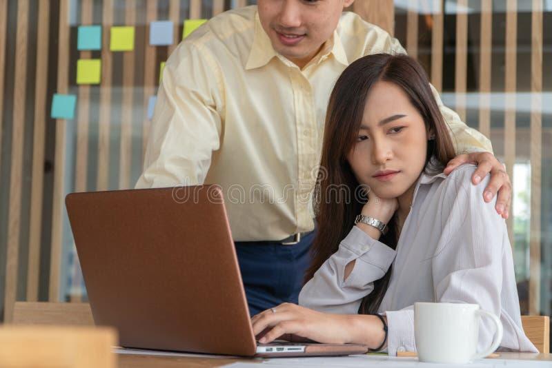 Homem de negócios que põe a mão sobre o ombro do empregado do sexo feminino no escritório no trabalho Ela infeliz e sentimento de imagens de stock