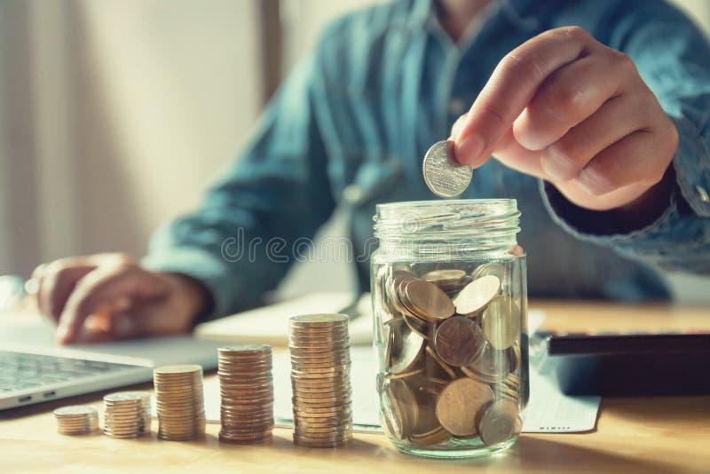 homem de negócios que põe moedas no vidro do jarro dinheiro da economia do conceito imagem de stock