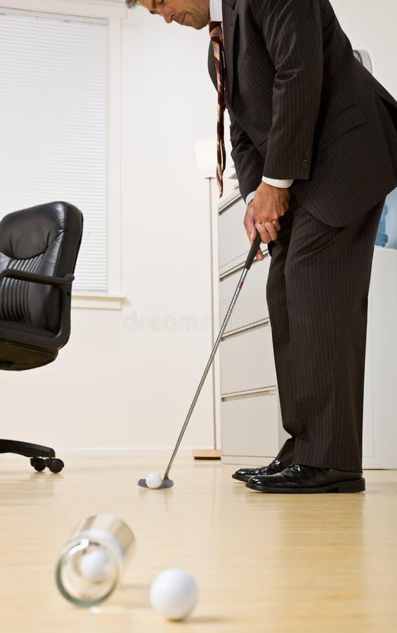Homem de negócios que põr a esfera de golfe no escritório foto de stock royalty free