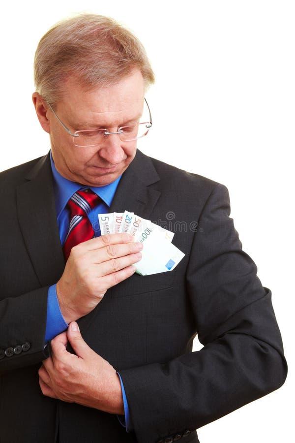 Homem de negócios que põr o dinheiro no bolso imagem de stock royalty free
