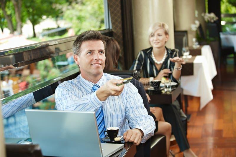 Homem de negócios que paga no café