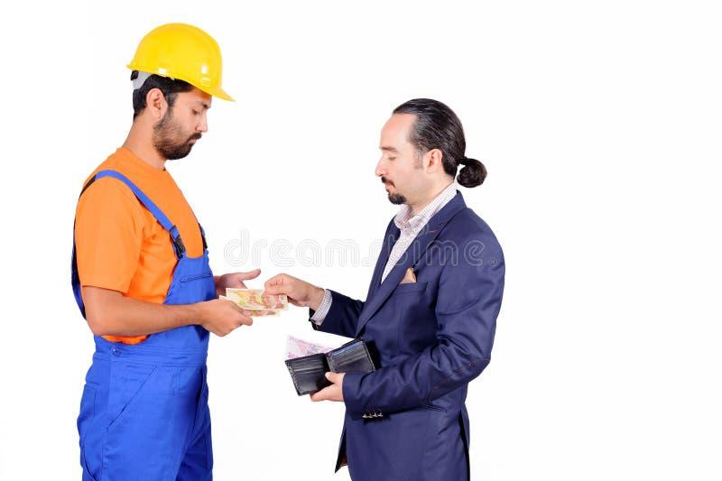 Homem de negócios que paga o trabalhador contratado do colarinho azul por serviços isolado no fundo branco imagens de stock royalty free