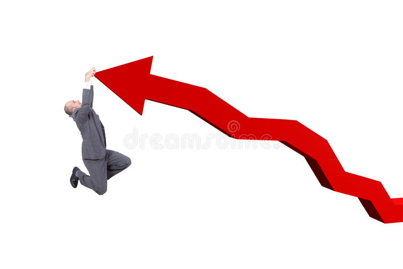 Homem de negócios que pendura em uma seta do gráfico fotografia de stock royalty free