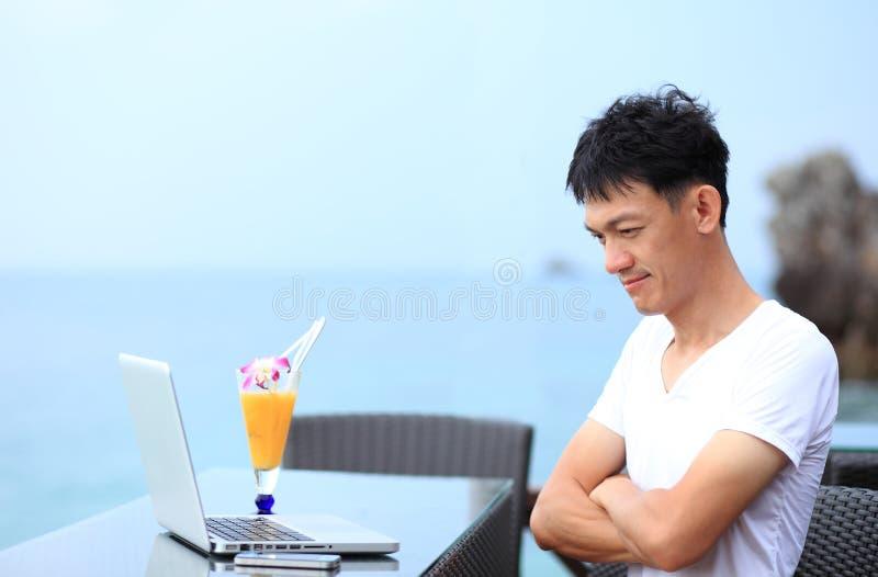 Homem de negócios que pensa com o portátil que senta-se na praia exterior fotos de stock royalty free