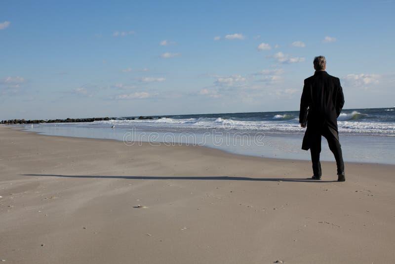 Homem de negócios que pensa na praia fotografia de stock royalty free