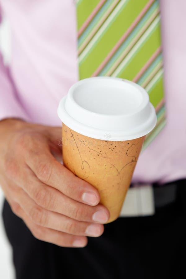 Homem de negócios que prende a chávena de café portátil fotografia de stock