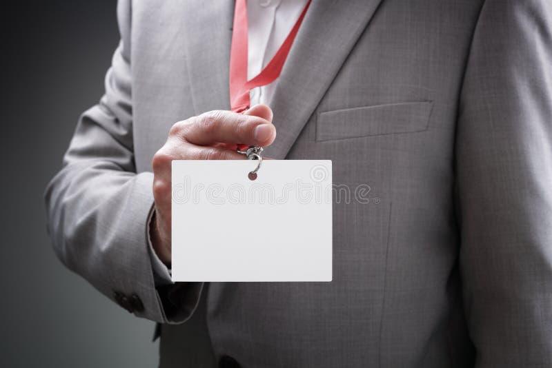 Homem de negócios que prende o emblema em branco da identificação foto de stock