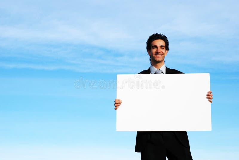 Homem de negócios que prende a placa em branco fotografia de stock