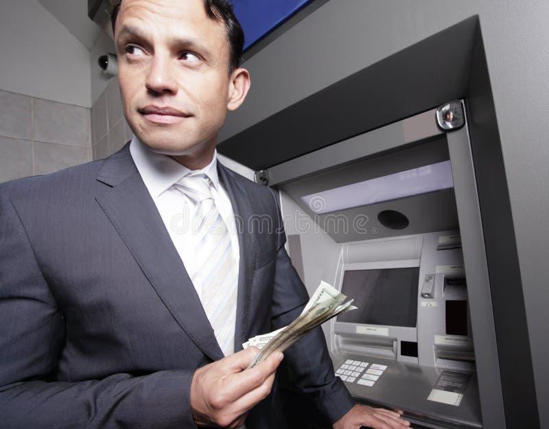 Homem de negócios que prende seu dinheiro fotos de stock royalty free
