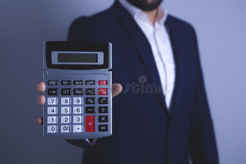 Homem de negócios que prende uma calculadora imagem de stock