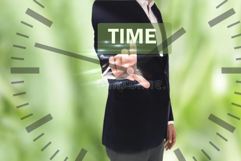 Homem de negócios que pressiona o botão do tempo em telas virtuais e em pulso de disparo imagem de stock