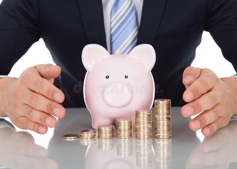 Homem de negócios que protege moedas e piggybank na mesa fotos de stock royalty free