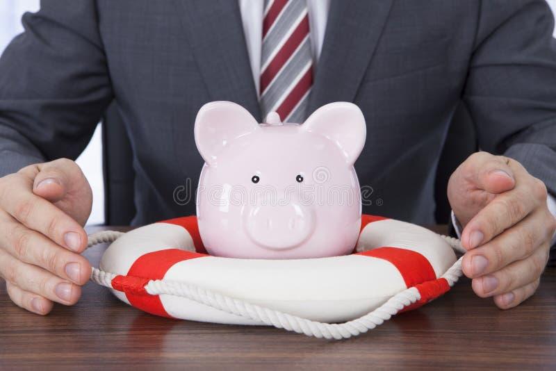 Homem de negócios que protege o piggybank com o cinto de salvação na mesa imagem de stock royalty free