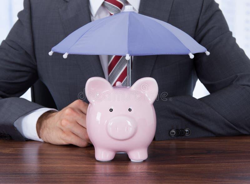 Homem de negócios que protege o piggybank com o guarda-chuva na mesa imagens de stock