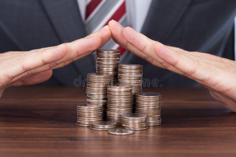 Homem de negócios que protege pilhas da moeda na tabela foto de stock royalty free
