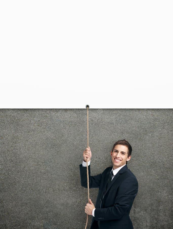 Homem de negócios que pulula acima da corda com cartaz branco imagens de stock royalty free