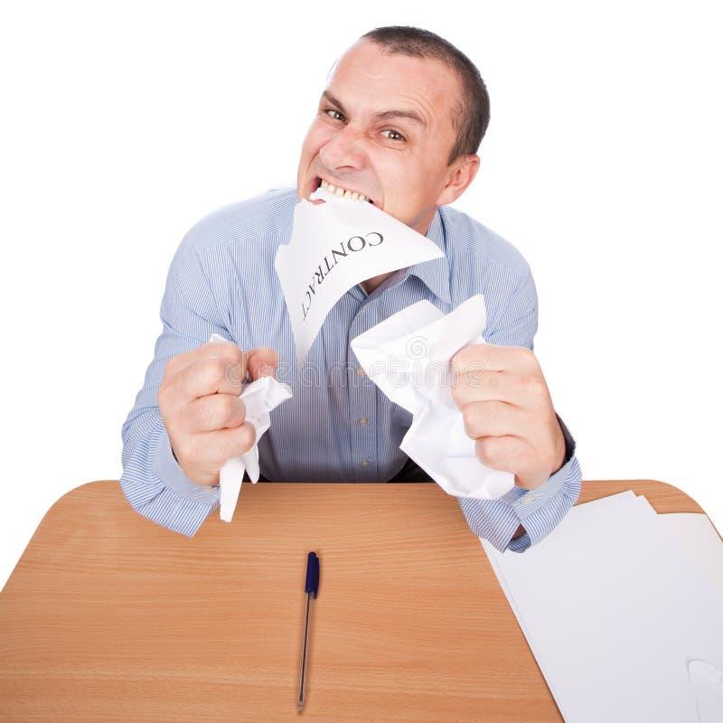 Homem de negócios que rasga distante o contrato com seus dentes imagens de stock