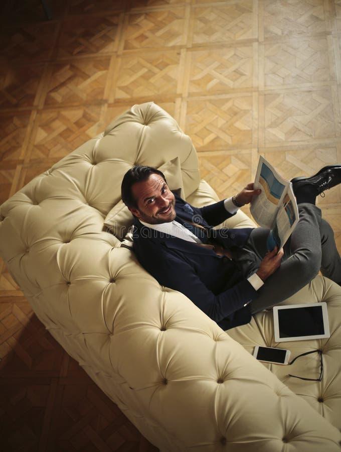 Homem de negócios que relaxa ao ler um compartimento foto de stock royalty free