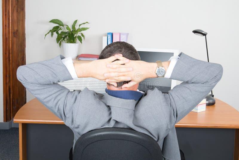 Homem de negócios que relaxa com mãos atrás da cabeça no escritório foto de stock