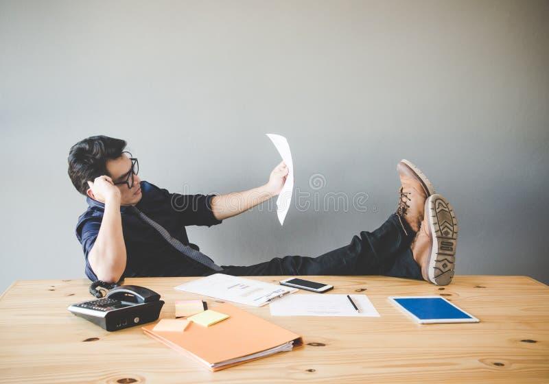 Homem de negócios que relaxa e que trabalha na mesa no escritório criativo fotos de stock