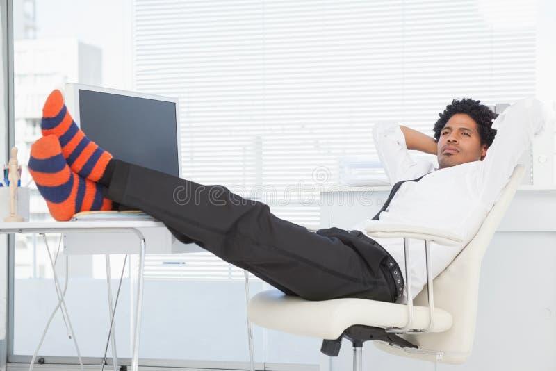 Homem de negócios que relaxa em sua cadeira de giro com pés acima imagens de stock royalty free