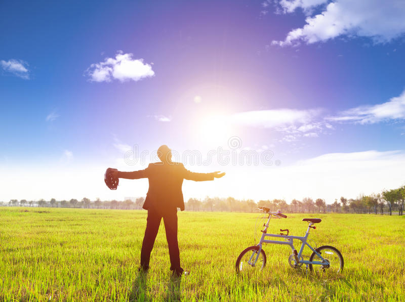 Homem de negócios que relaxa na terra e no sol verdes com bicicleta fotografia de stock royalty free