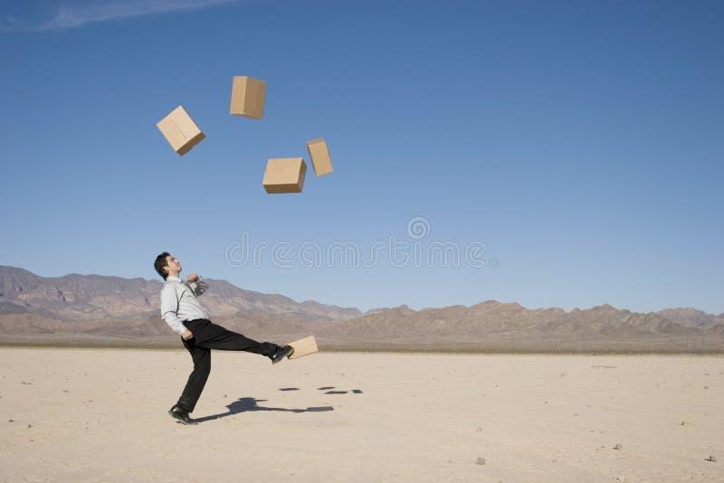 Homem de negócios que retrocede caixas fotos de stock