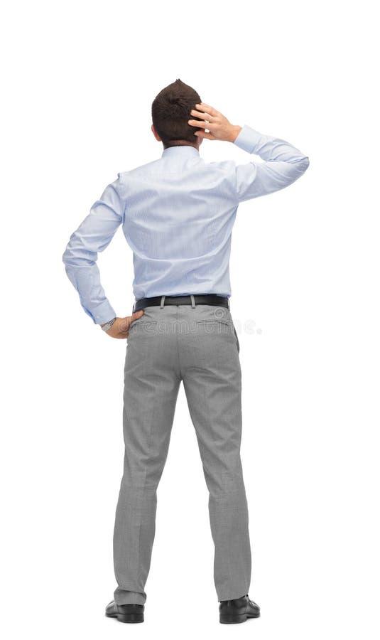 Homem de negócios que risca sua cabeça da parte traseira fotografia de stock royalty free