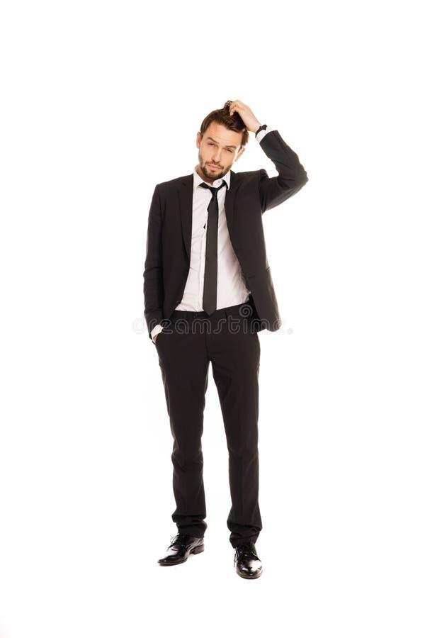 Homem de negócios que risca sua cabeça na dúvida foto de stock