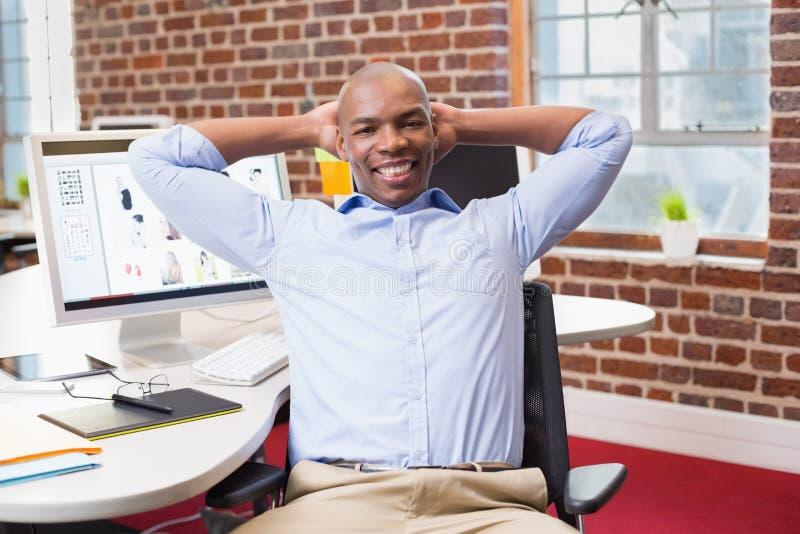 Homem de negócios que senta-se com mãos atrás da cabeça no escritório fotografia de stock royalty free