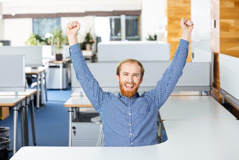 Homem de negócios que senta-se com mãos levantadas e que comemora o sucesso no escritório imagem de stock royalty free