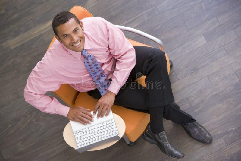 Homem de negócios que senta-se dentro com sorriso do portátil foto de stock royalty free