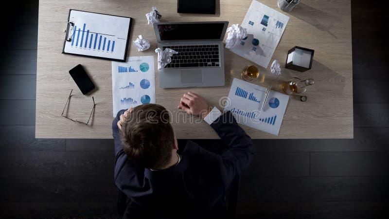 Homem de negócios que senta-se em seu escritório que pensa sobre o álcool bebendo, depressão imagens de stock royalty free