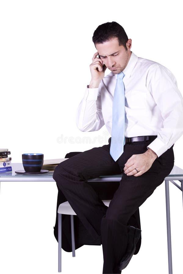Homem de negócios que senta-se em sua mesa imagem de stock royalty free