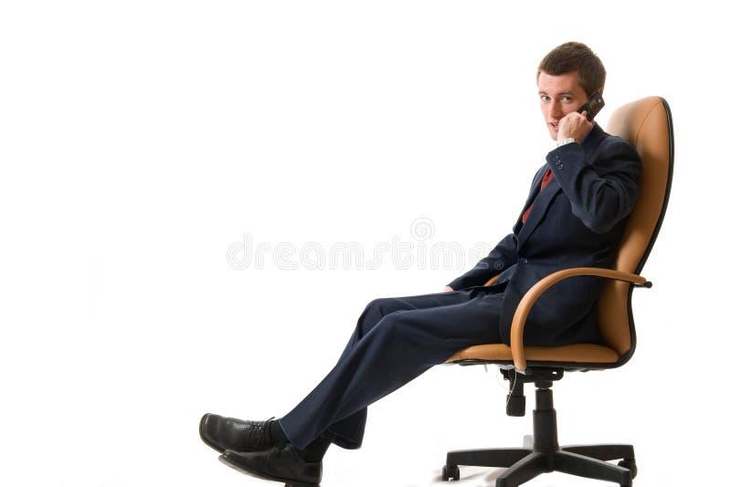 Homem de negócios que senta-se em uma poltrona fotografia de stock