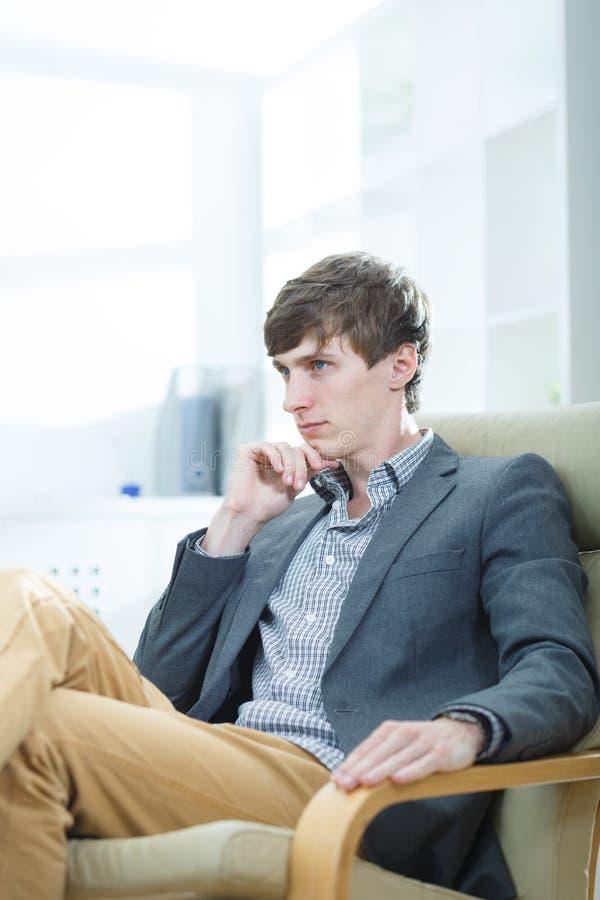 Homem de negócios que senta-se em uma poltrona imagem de stock