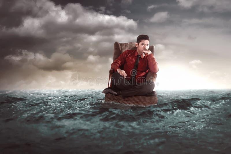 Homem de negócios que senta-se em uma poltrona no meio do mar imagem de stock