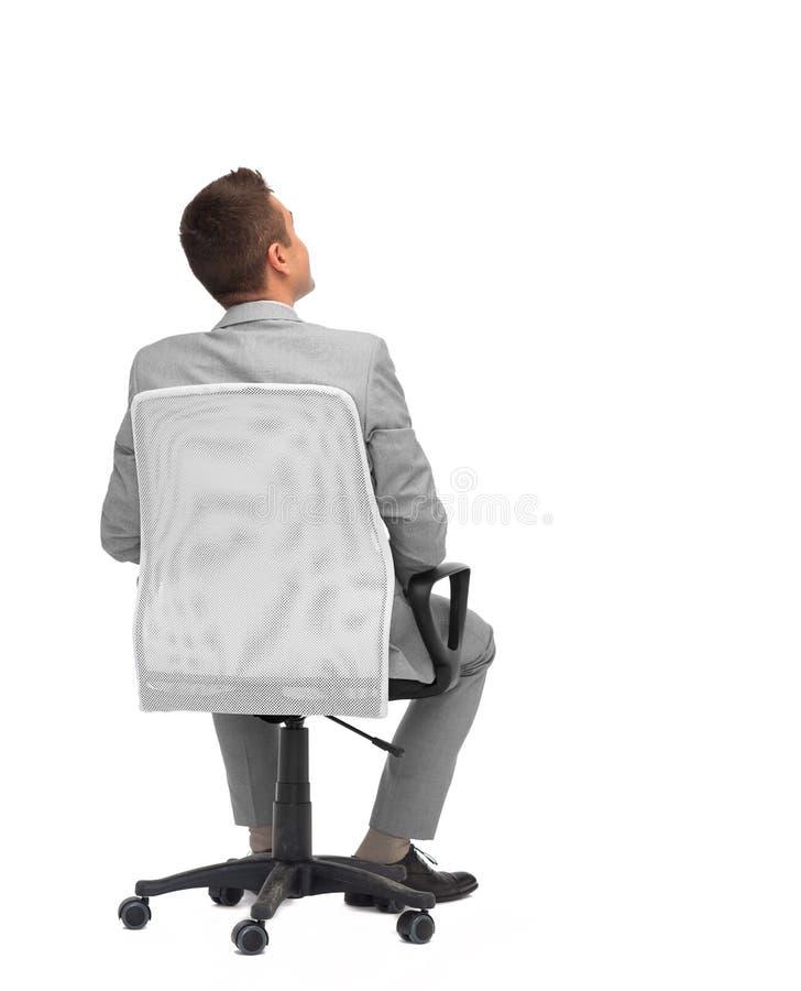 Homem de negócios que senta-se na cadeira do escritório da parte traseira foto de stock