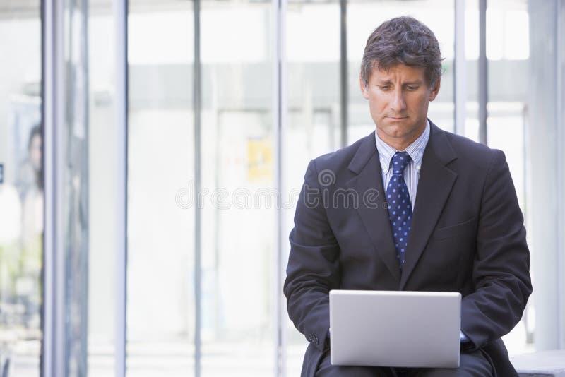 Homem de negócios que senta-se na entrada do escritório usando o portátil fotos de stock