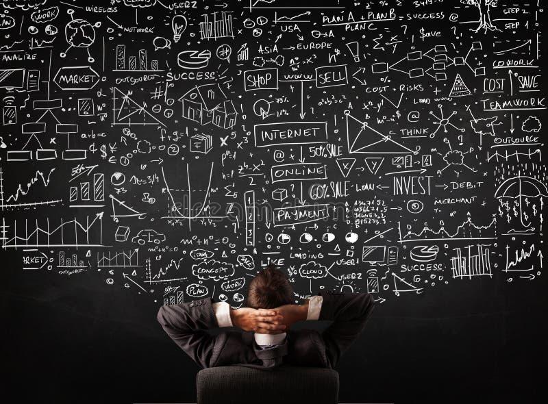 Homem de negócios que senta-se na frente de um quadro-negro com cartas fotos de stock