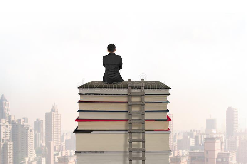Homem de negócios que senta-se na pilha de livros com escada de madeira fotografia de stock