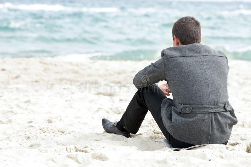 Homem de negócios que senta-se na praia sozinho imagens de stock royalty free