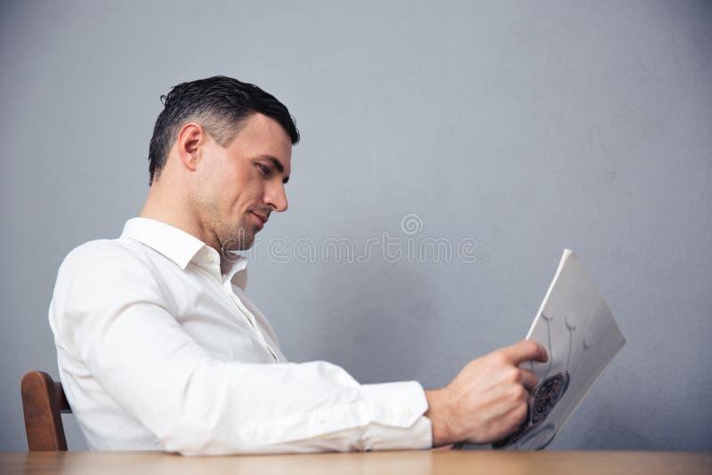 Homem de negócios que senta-se na tabela e que lê o compartimento imagem de stock