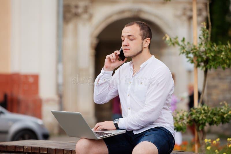Homem de negócios que senta-se no citypark usando o telefone celular e o portátil foto de stock