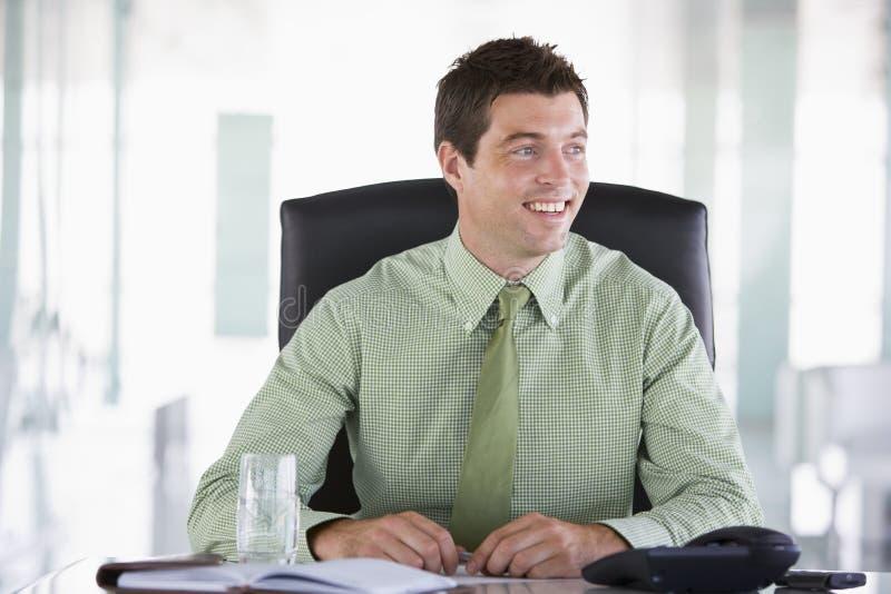 Homem de negócios que senta-se no escritório com organi pessoal fotos de stock royalty free