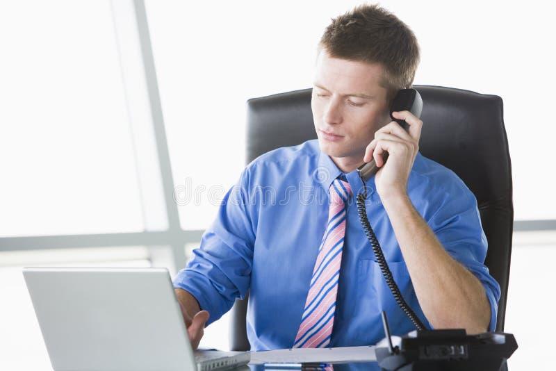 Homem de negócios que senta-se no escritório com portátil fotografia de stock royalty free